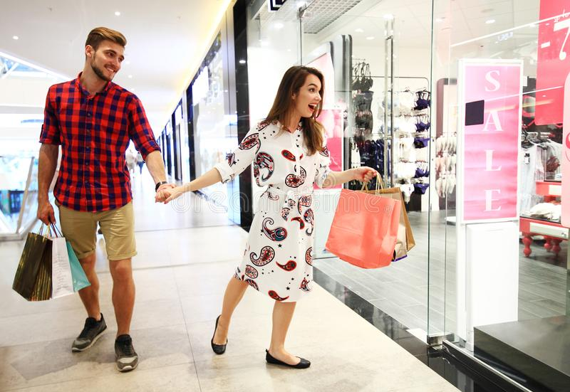 Sale, consumerism and people concept - happy young couple with shopping bags walking in mall. stock photo