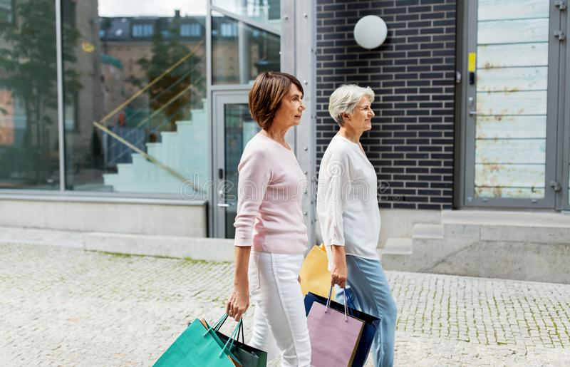 Senior women with shopping bags walking in city royalty free stock photos