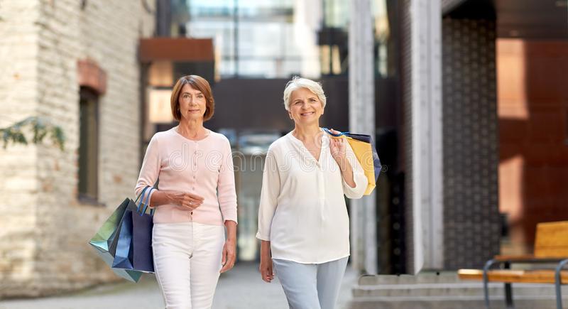 Senior women with shopping bags walking in city stock photo