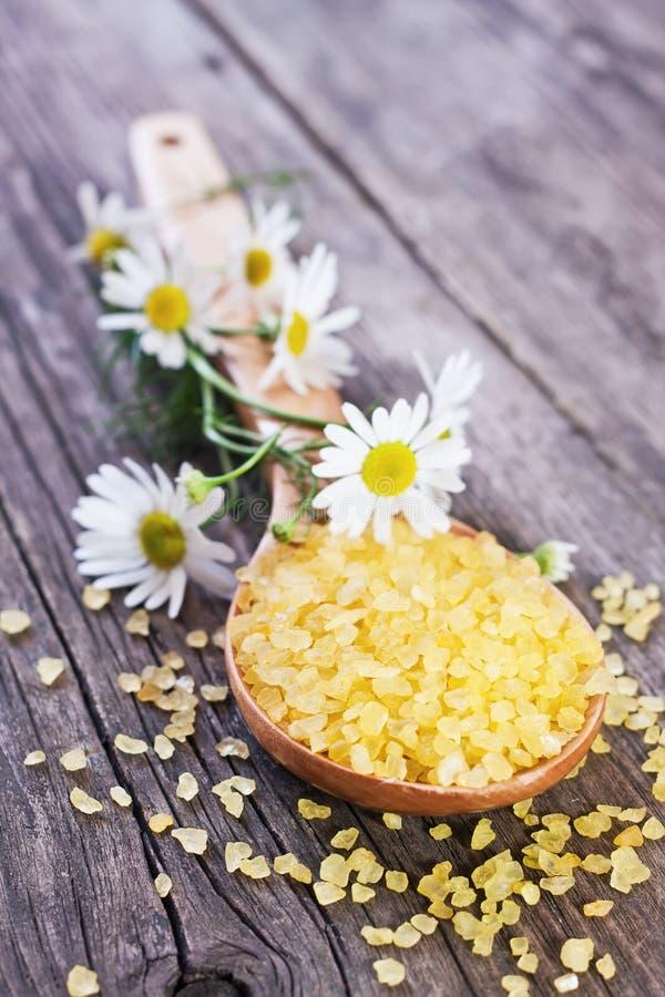 Sale di bagno giallo sul cucchiaio di legno fotografia stock