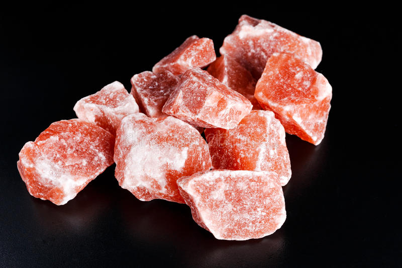 Sale di cristallo rosa himalayano su fondo scuro fotografie stock