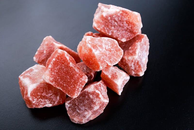 Sale di cristallo rosa himalayano su fondo scuro fotografia stock