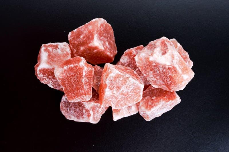 Sale di cristallo rosa himalayano su fondo scuro fotografia stock libera da diritti