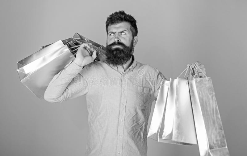 Sale and discount concept. Guy shopping on sales season with discounts. Hipster on strict face shopping addicted or. Shopaholic. Man with beard and mustache stock photography