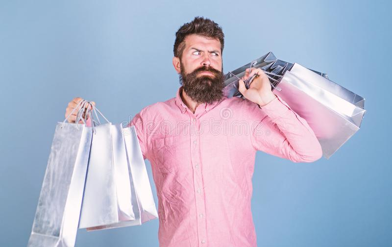 Sale and discount concept. Guy shopping on sales season with discounts. Hipster on strict face shopping addicted or. Shopaholic. Man with beard and mustache royalty free stock photography