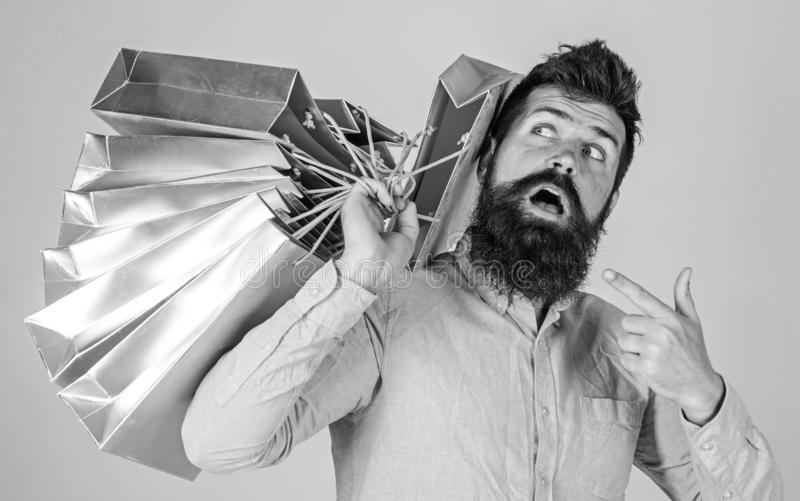 Sale and discount concept. Guy shopping on sales season, pointing at bags. Hipster on surprised face addicted shopaholic. Man with beard and mustache carries stock photo