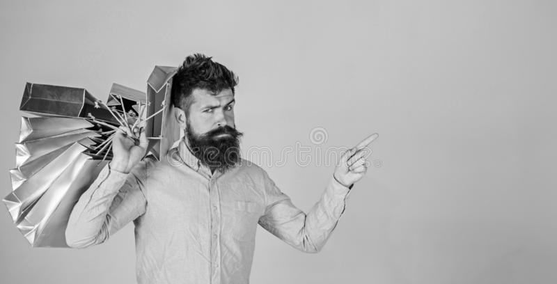 Sale and discount concept. Guy shopping on sales season, pointing with finger. Hipster on serious face addicted. Shopaholic. Man with beard and mustache carries royalty free stock photo