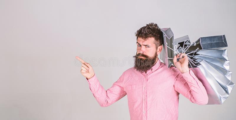 Sale and discount concept. Guy shopping on sales season, pointing with finger. Hipster on serious face addicted. Shopaholic. Man with beard and mustache carries stock photography