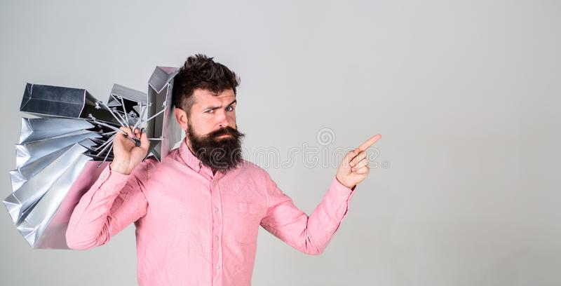 Sale and discount concept. Guy shopping on sales season, pointing with finger. Hipster on serious face addicted. Shopaholic. Man with beard and mustache carries royalty free stock image