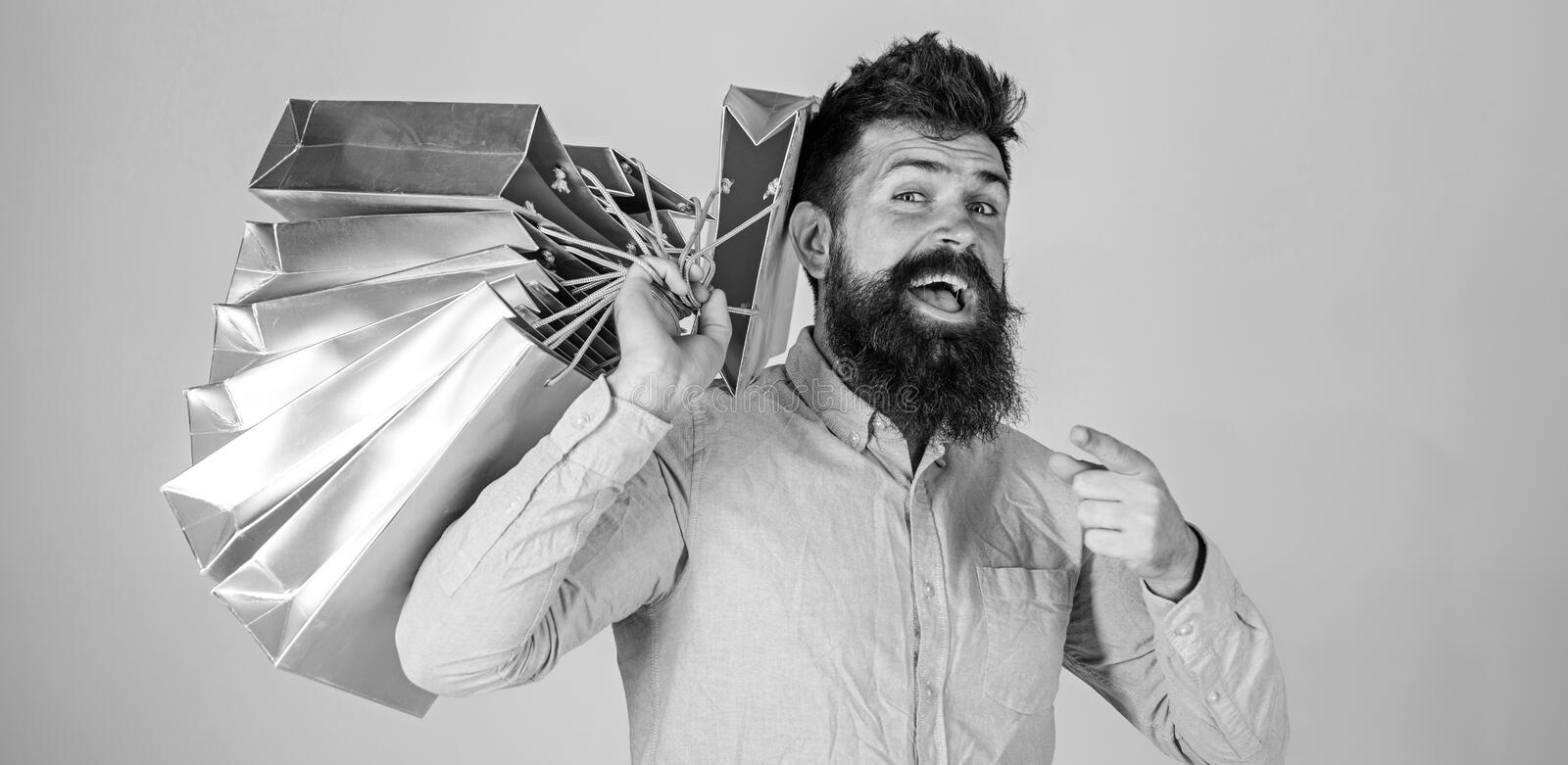 Sale and discount concept. Guy shopping on sales season, pointing forward. Hipster on happy face addicted shopaholic. Man with beard and mustache carries bunch royalty free stock image
