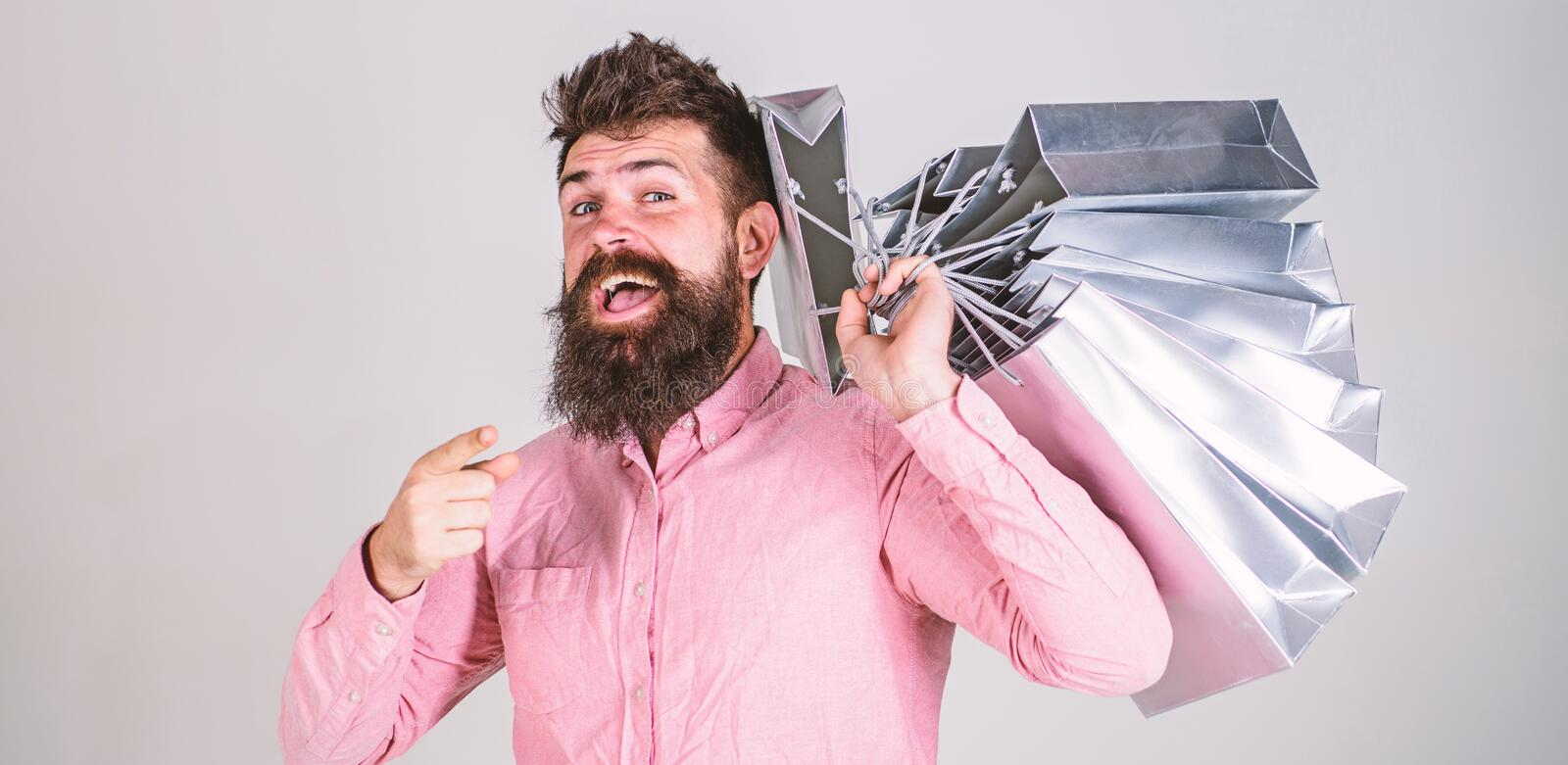 Sale and discount concept. Guy shopping on sales season, pointing forward. Hipster on happy face addicted shopaholic. Man with beard and mustache carries bunch royalty free stock photo