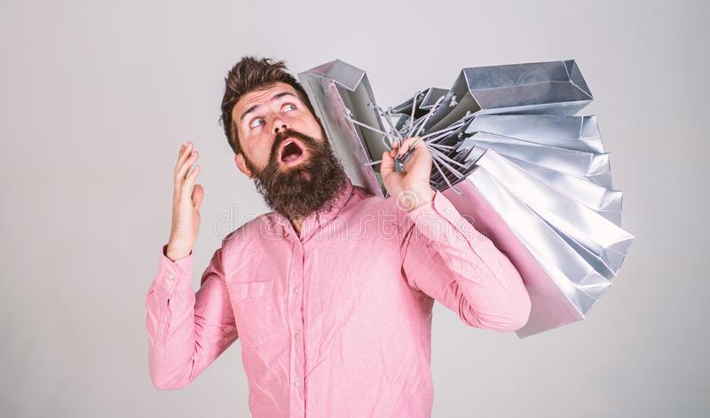 Sale and discount concept. Guy shopping on sales season, wondering of bags. Hipster on surprised face addicted. Shopaholic. Man with beard and mustache carries stock photo
