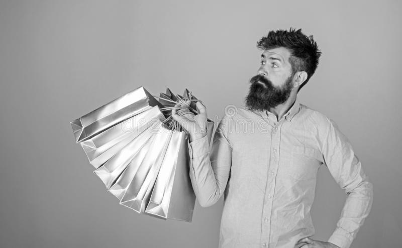 Sale and discount concept. Hipster on serious face carries shopping bags. Guy shopping on sales season with discounts. Man with beard and mustache works as stock photography