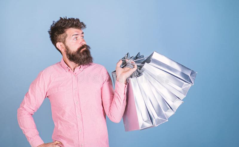 Sale and discount concept. Hipster on serious face carries shopping bags. Guy shopping on sales season with discounts. Man with beard and mustache works as royalty free stock photography
