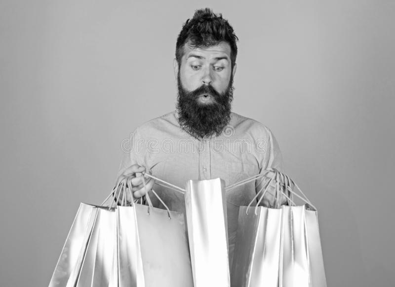 Sale and discount concept. Hipster on shocked face shopping addicted or shopaholic. Guy shopping on sales season with. Discounts. Man with beard and mustache stock photography