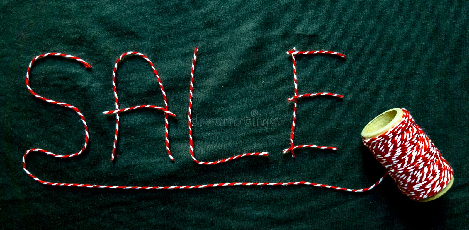 Sale, discount word made of red thread with a spool on a black background. Background, holiday concept. Black Friday -. International Day of Shopping stock photo