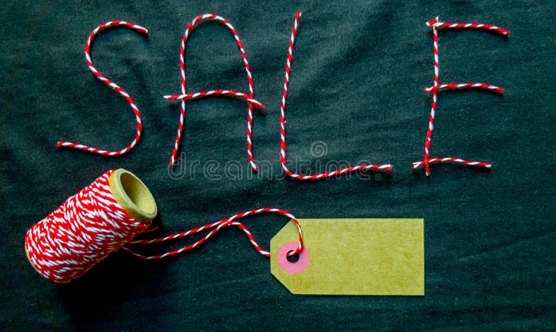 Sale, discount word made of red thread with a spool on a black background. Background, holiday concept. Black Friday -. International Day of Shopping royalty free stock images