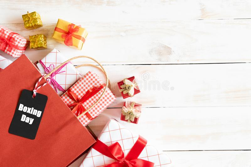Sale för boxningdag text på en svart etikett med shoppingpåsen och gåvaask på en trävit bakgrund card grund shopping för dof-foku arkivfoto