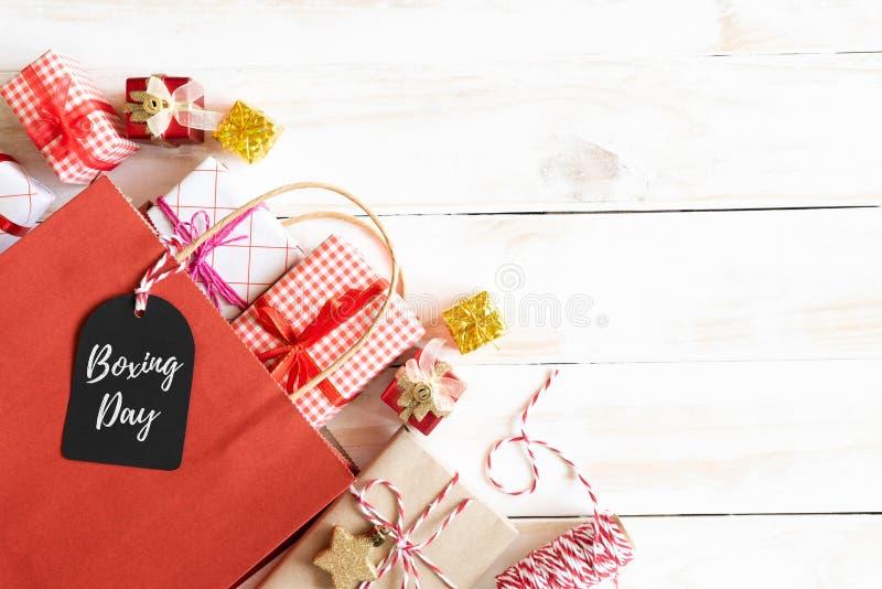 Sale för boxningdag text på en svart etikett med shoppingpåsen och gåvaask på en trävit bakgrund card grund shopping för dof-foku royaltyfria foton