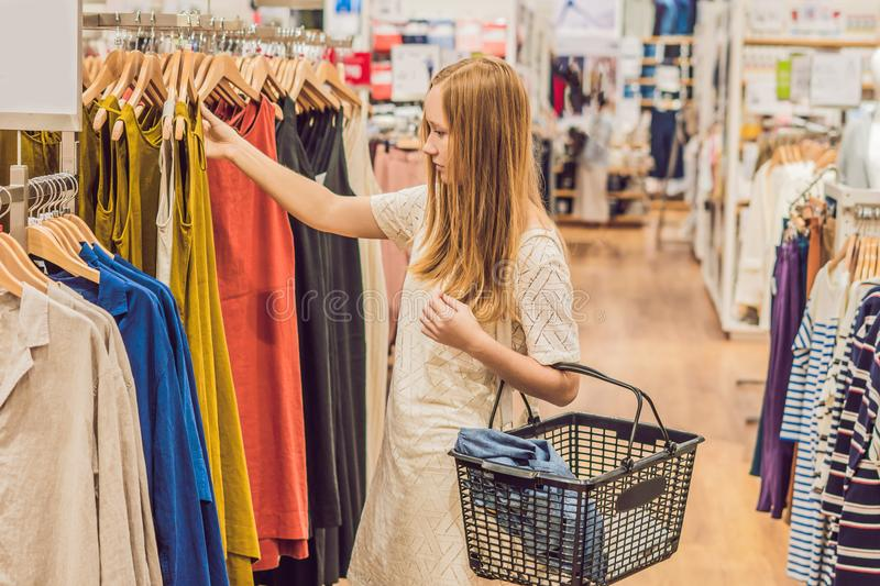 Sale, fashion, consumerism and people concept - happy young woman with shopping bags choosing clothes in mall or clothing store stock photos