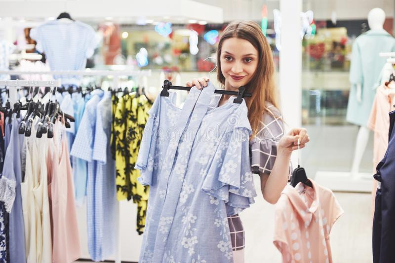 Sale, fashion, consumerism and people concept - happy young woman with shopping bags choosing clothes in mall or royalty free stock photography