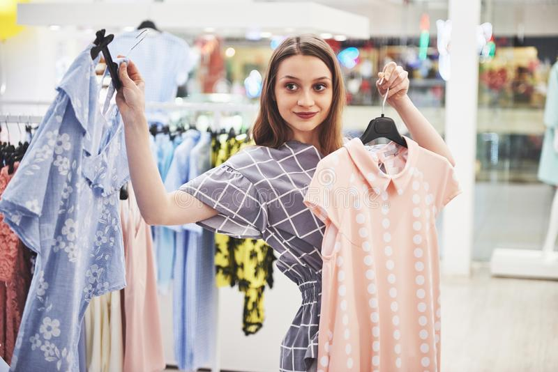 Sale, fashion, consumerism and people concept - happy young woman with shopping bags choosing clothes in mall or stock photo