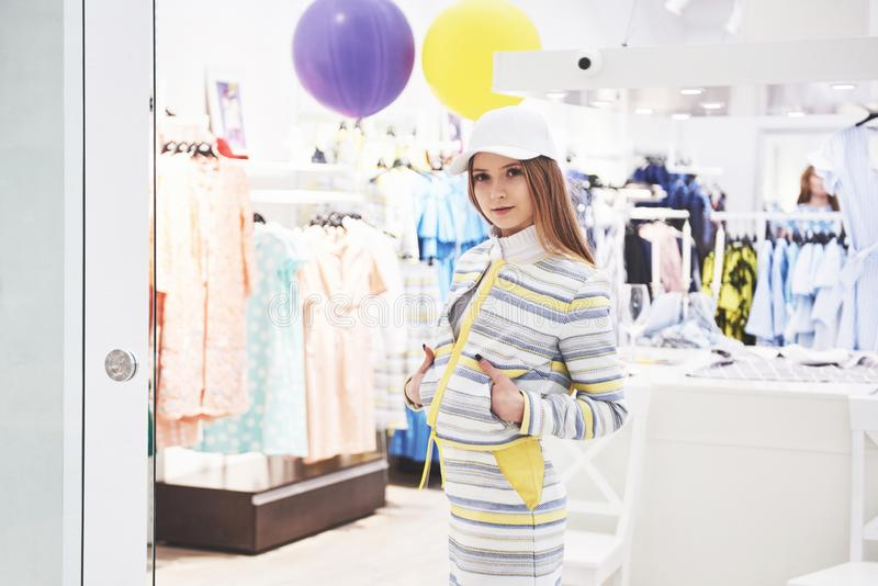 Sale, fashion, consumerism and people concept - happy young woman with shopping bags choosing clothes in mall or royalty free stock photo