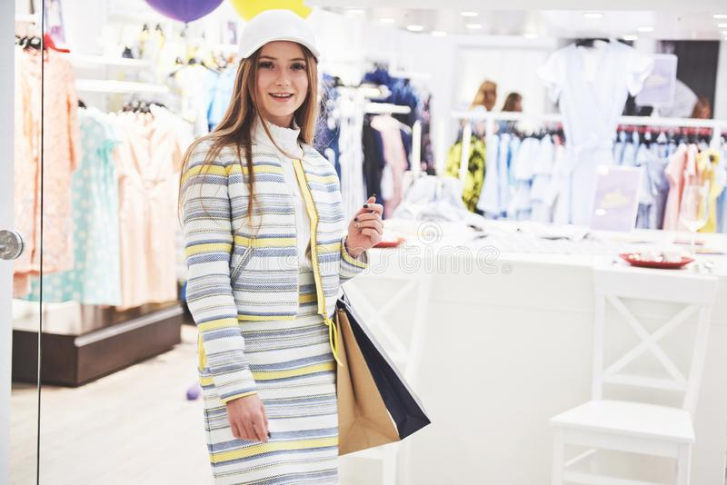 Sale, fashion, consumerism and people concept - happy young woman with shopping bags choosing clothes in mall or royalty free stock image