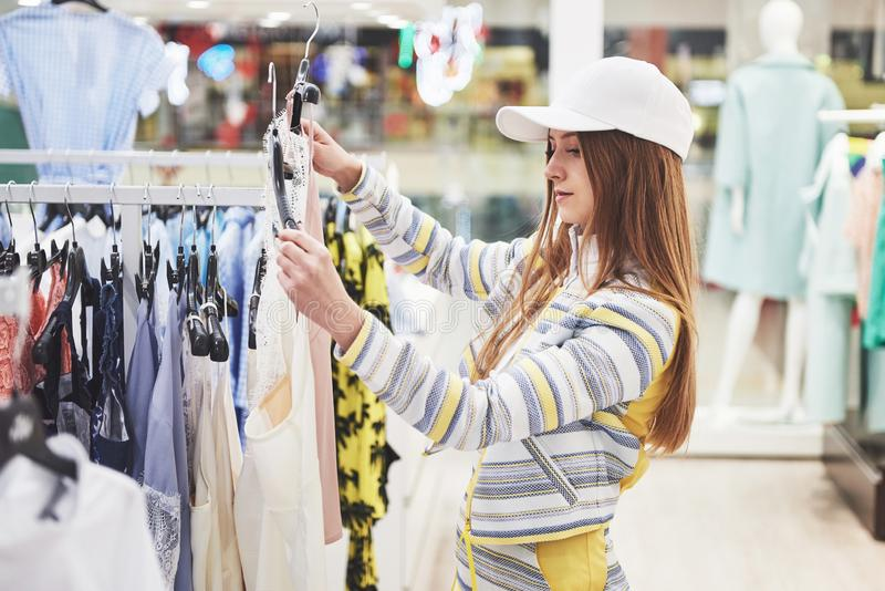 Sale, fashion, consumerism and people concept - happy young woman with shopping bags choosing clothes in mall or royalty free stock photos