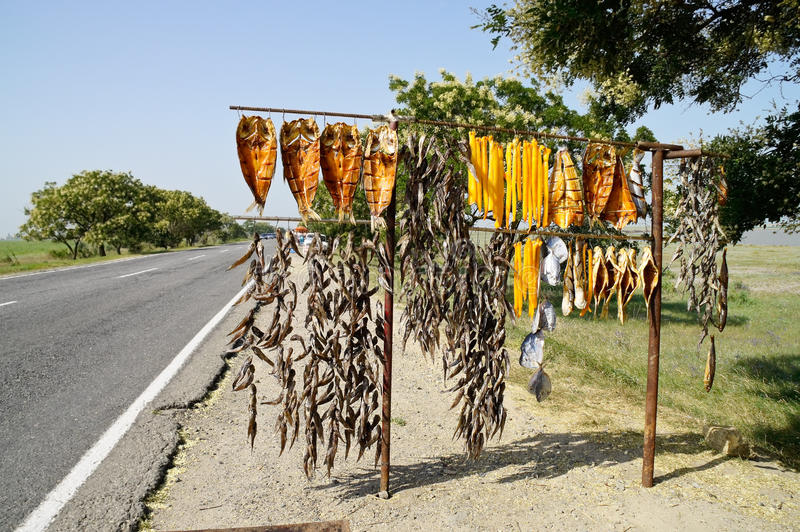 Sale of fish on the track. Sale of smoked fish on the background of the road stock photography