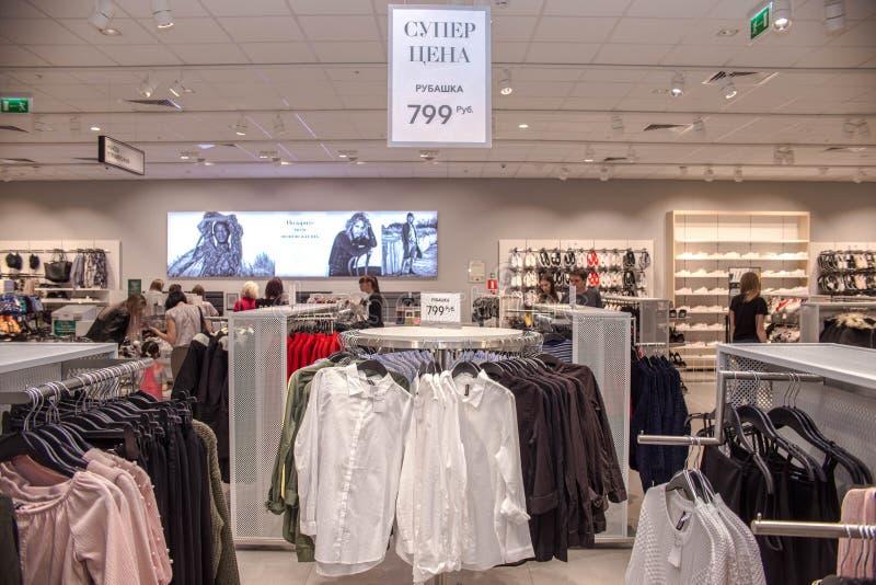 Sale i detaljhandeln för det bekläda lagret, skyltdockor är på räknaren av lagret, folk gör köp i lagret, shopping arkivbild