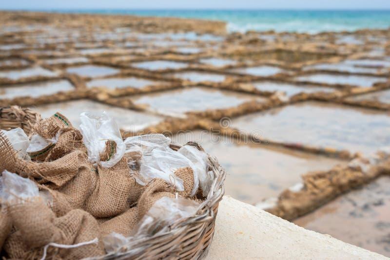 Sale los bolsos cosechados de saltpans que es showen en el fondo en Marsalforn Gozo fotografía de archivo libre de regalías