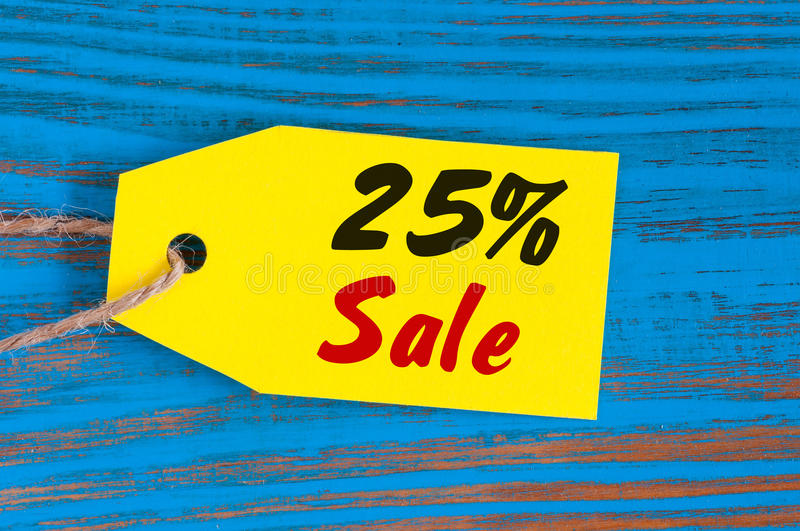 Sale minus 25 percent. Big sales twenty five percents on blue wooden background for flyer, poster, shopping, sign royalty free stock photography