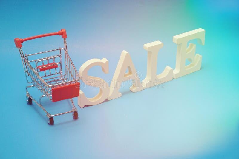 Sale och Mini Trolley Cart på blå bakgrund arkivfoto