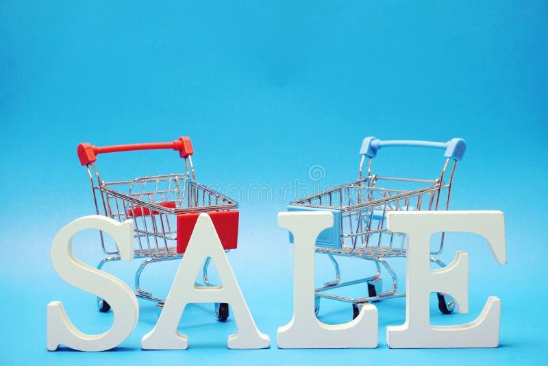 Sale och Mini Trolley Cart p? bl? bakgrund arkivfoton