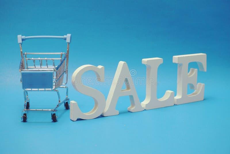 Sale och Mini Trolley Cart p? bl? bakgrund royaltyfri bild