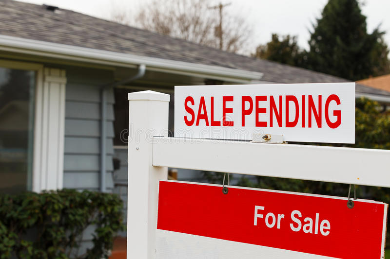 Sale Pending Real Estate Sign. Real estate sign says for sale and pending on the top of it in front of a grey house stock images
