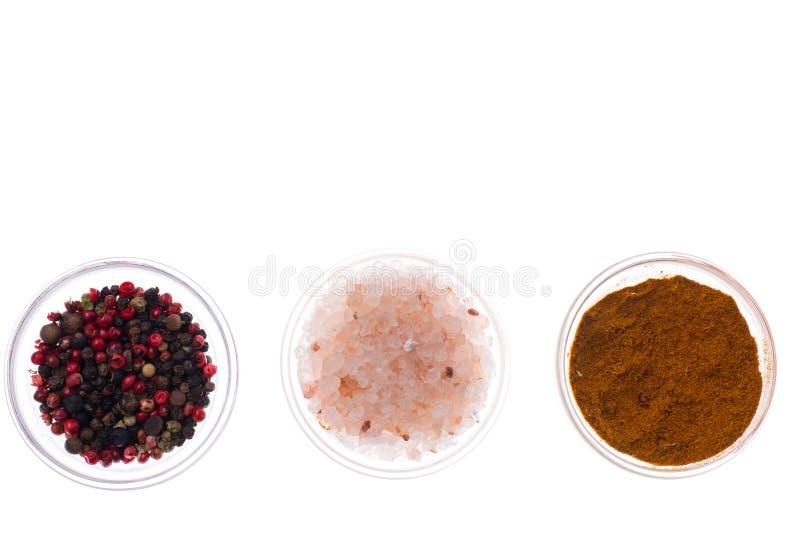 Sale, pepe nero e curry in vetro isolato sul backgrou bianco immagine stock