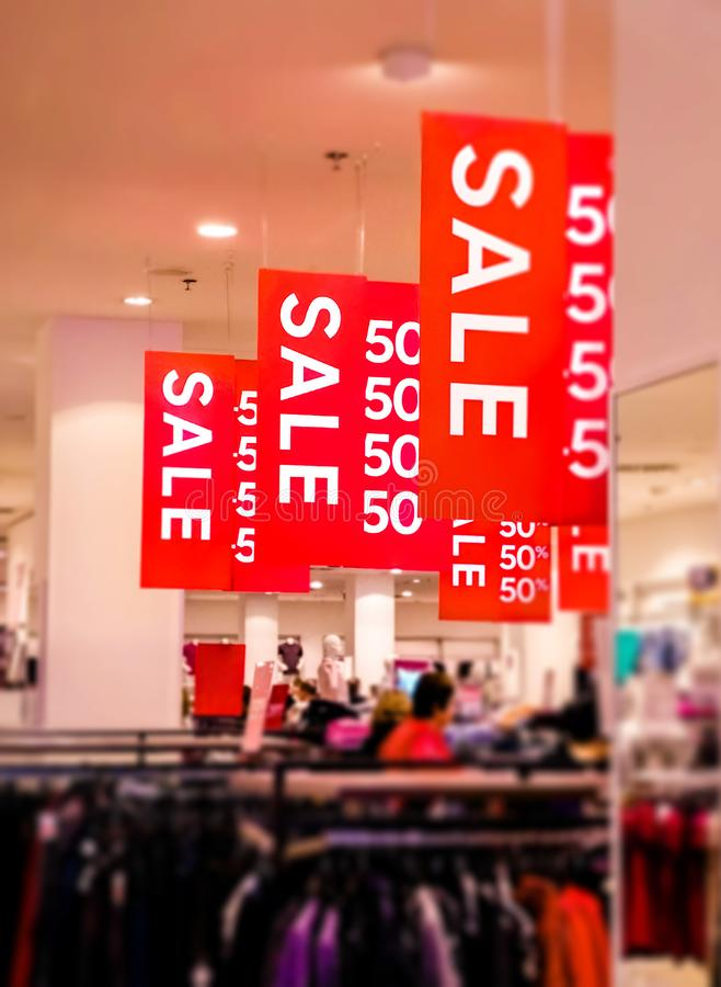 Sale posters with white letters. Hang from grid ceiling in big shop in sale season royalty free stock photography