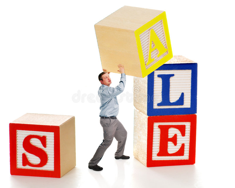 SALE Prep. Business man creating a SALE sign out of giant alphabet blocks royalty free stock photos