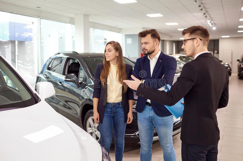 Sale, rental cars. A car dealer sells cars to customers. Sale, rental cars.A couple buys a car at a car dealership. A car dealer sells cars to customers royalty free stock images
