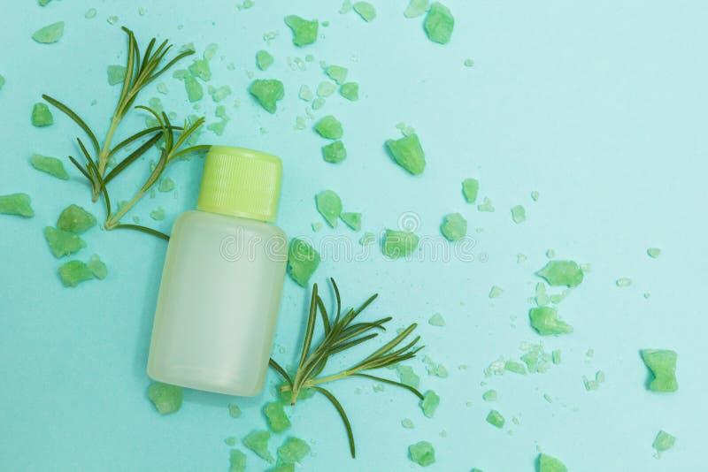 Sale, rosmarini e bottiglia di erbe verdi di olio essenziale su un fondo blu fotografia stock