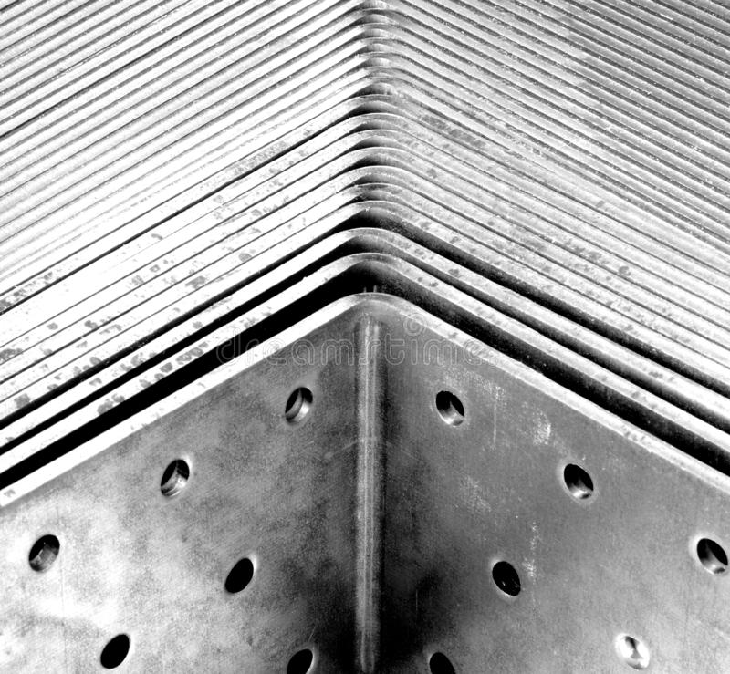 Sale shelf with hole plate angle. New galvanized angle connectors, angular wood connectors in galvanized with nail holes, Punch plate angle in the sales box royalty free stock photography