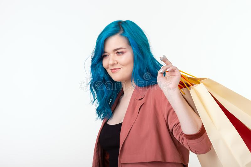 Sale, shopaholic and consumer concept - beautiful girl with blue hair standing with shopping bags on white background royalty free stock photos