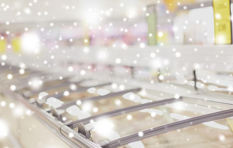 Freezers at grocery store. Sale, shopping, consumerism and storage concept - freezers at grocery store over snow royalty free stock images