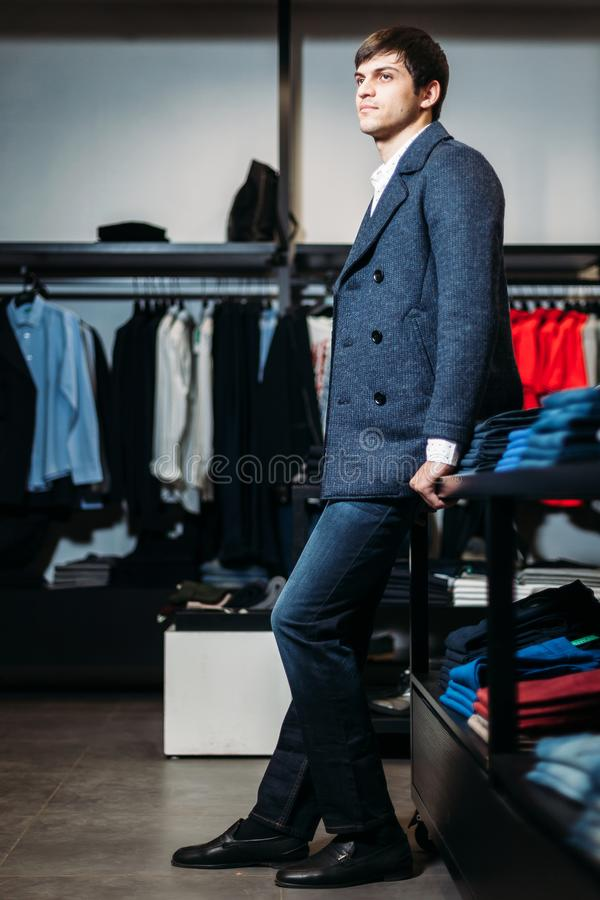 Sale, shopping, fashion, style and people concept - elegant young man in coat stands in a clothing store. sign for clothing store royalty free stock photos
