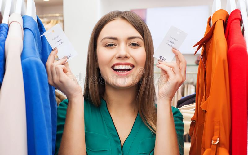 Happy woman with price tags at clothing store royalty free stock photography