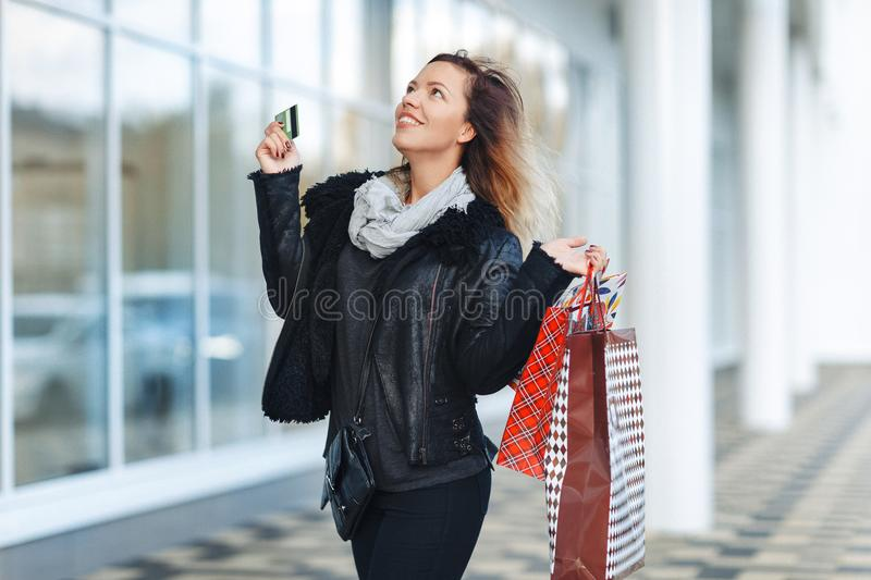 Sale, shopping, tourism and happy people concept - beautiful woman with shopping bags and credit card in the hands on a street. royalty free stock photo