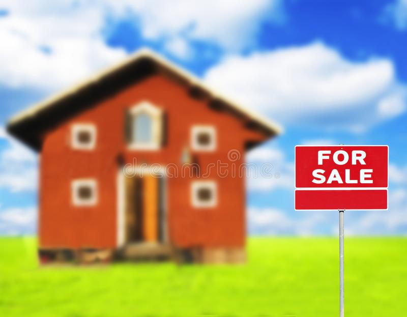 \'FOR SALE\' sign against wooden house on beautiful meadow in background stock image