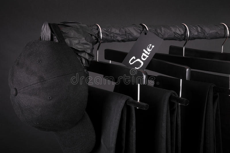 Sale sign. Black cap and pant, jeans hanging on clothes rack background. friday. Close up. Sale sign. Black cap and pant, jeans hanging on clothes rack on black stock photo